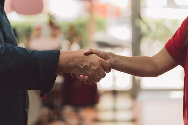 Uomo e donna che si stringono la mano in segno di accordo