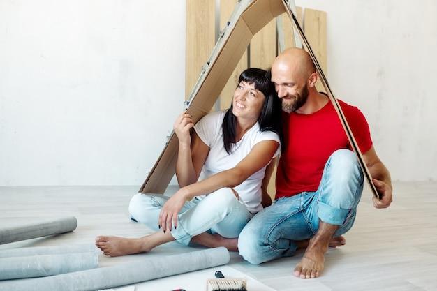Un uomo e una donna si siedono per terra in un nuovo appartamento durante i lavori di ristrutturazione e tengono un tetto di cartone sopra le loro teste