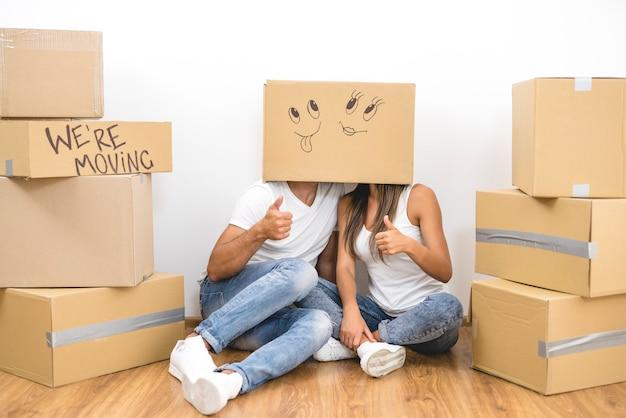 L'uomo e la donna si siedono sul pavimento con una scatola di cartone sulla testa e fanno un gesto