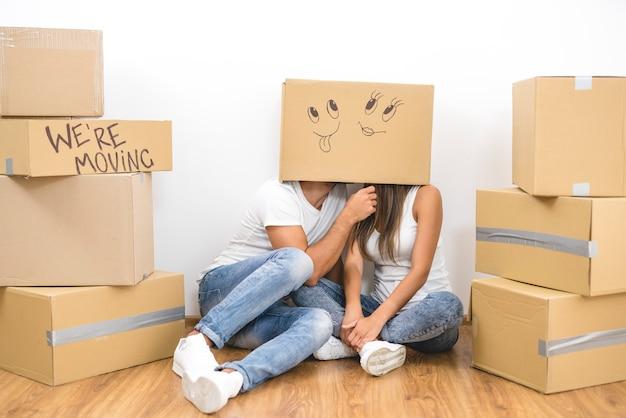 L'uomo e la donna si siedono sul pavimento con una scatola di cartone sulla testa