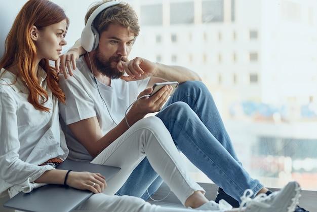 L'uomo e la donna si siedono vicino alla finestra con le cuffie amano la tecnologia lifestyle