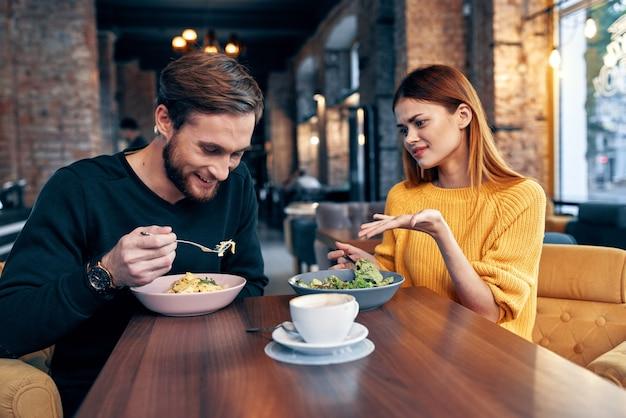 Uomo e donna che si siedono in un romanticismo di stile di vita dello spuntino di comunicazione del caffè