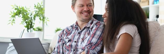 Uomo e donna seduti sul divano con il laptop