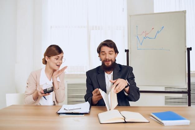 Uomo e donna seduti alla scrivania, emozioni di comunicazione, insoddisfazione dei colleghi di lavoro