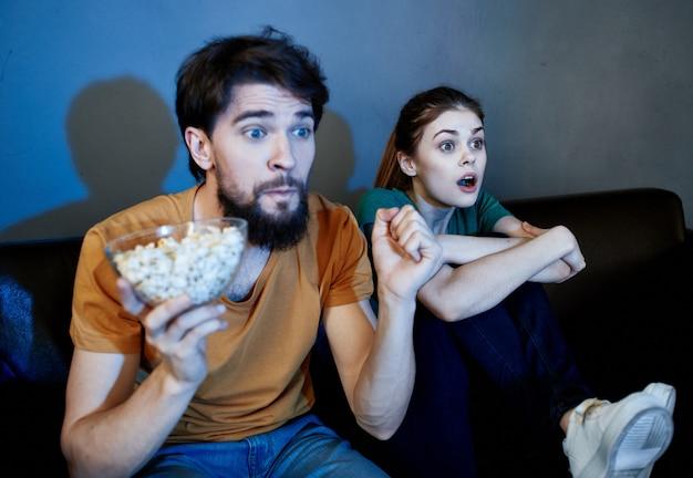 Uomo e una donna seduta sul divano davanti alla tv al chiuso