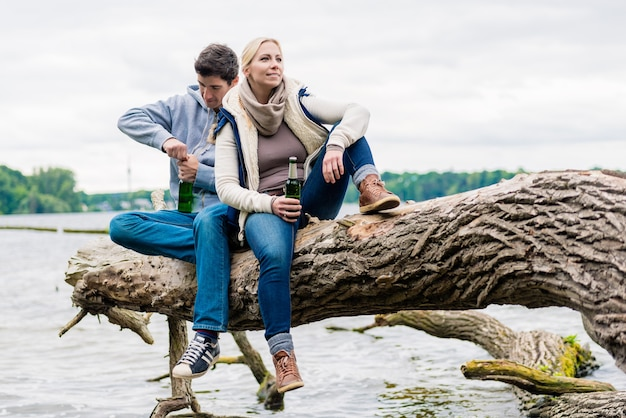 Uomo e donna che si siedono sul tronco vicino al lago e bevono birra in bottiglia