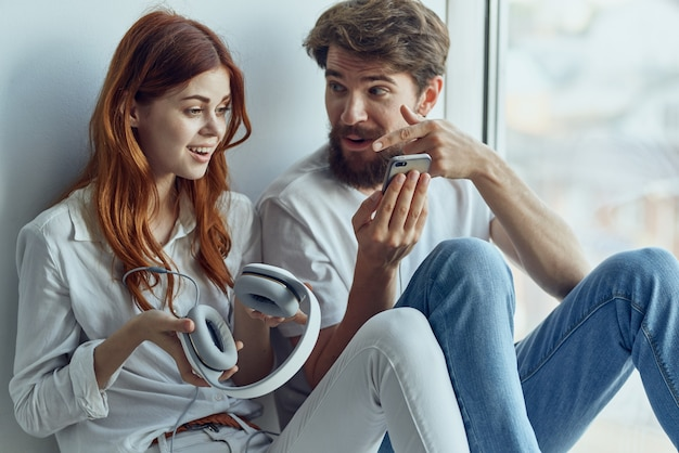 Uomo e donna seduti sul davanzale della finestra insieme tecnologia degli appartamenti