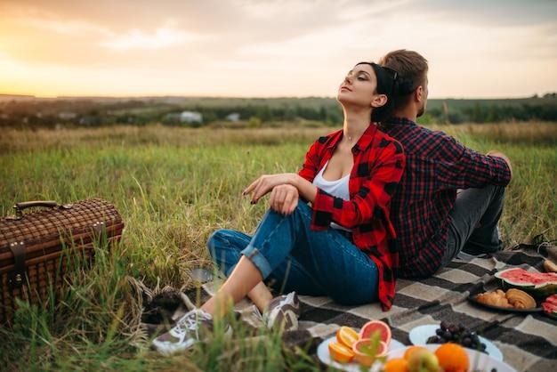 Uomo e donna seduti con le spalle l'un l'altro al tramonto, picnic nel campo. giuncata romantica al tramonto, coppia a cena all'aperto, relazioni felici