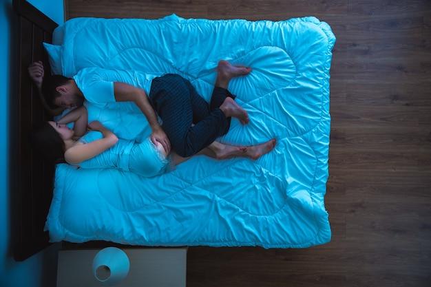 L'uomo e una donna che dormono sul letto. sera notte, vista dall'alto