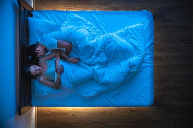 L'uomo e una donna che dormono sul letto. vista dall'alto, serale notturno