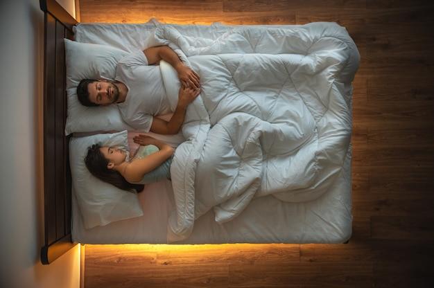 L'uomo e una donna che dormono sul letto. vista dall'alto