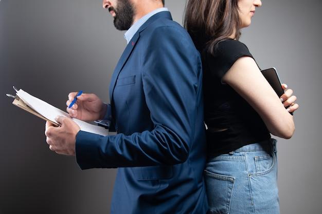 L'uomo e la donna stanno schiena contro schiena. soci in affari