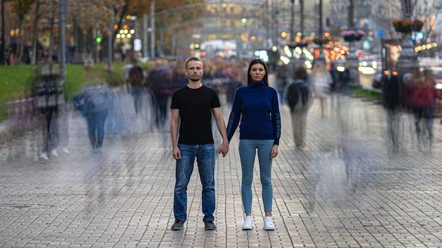 L'uomo e la donna stanno sulla strada affollata e si tengono per mano