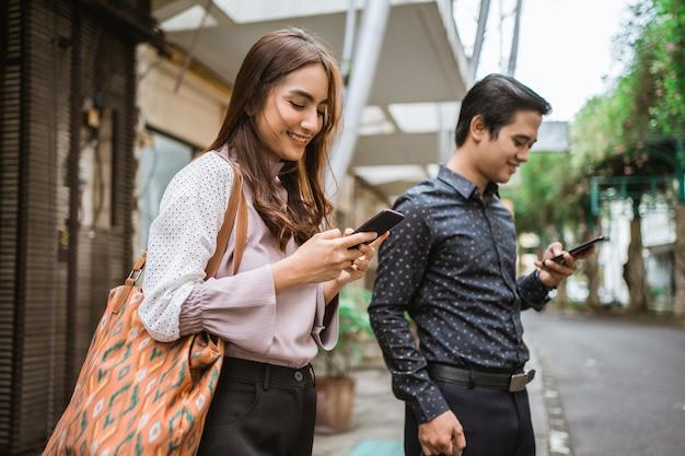 Uomo e donna in piedi su un marciapiede sorridenti usando il telefono