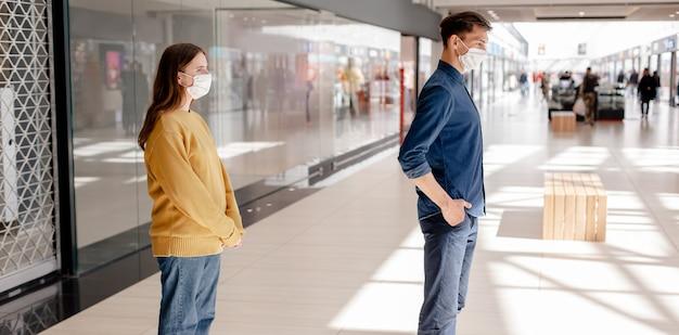 Un uomo e una donna in piedi in un supermercato a distanza di sicurezza. concetto di tutela della salute.