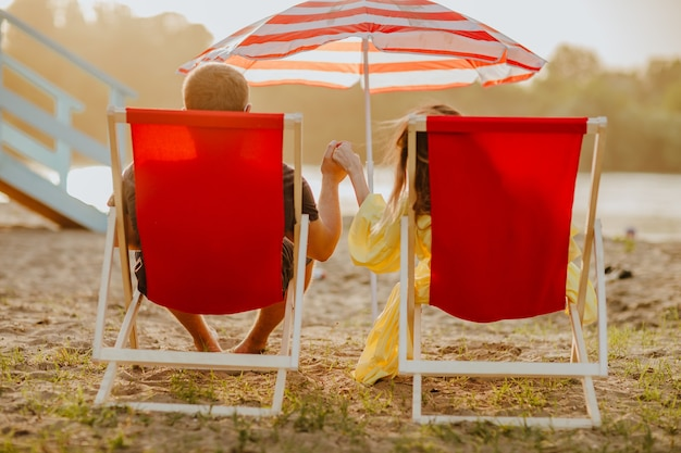 Uomo e donna in abiti estivi sdraiati su sedie a sdraio rosse sulla spiaggia di sabbia durante il tramonto. il focus è a portata di mano. vista dal retro.