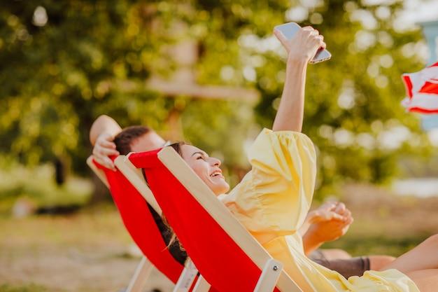 Uomo e donna in abiti estivi sdraiati su sedie a sdraio rosse sulla spiaggia di sabbia durante il tramonto e facendo selfie al telefono.