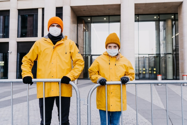 Uomo e donna in maschere chirurgiche in piedi dietro il recinto durante la quarantena, in attesa di aiuto da parte del governo o della gente. blocco durante il concetto di pandemia 19 covid.