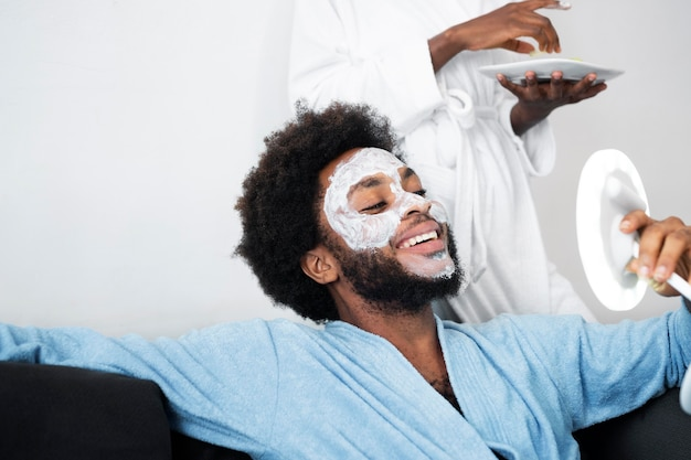 Uomo e donna che si prendono cura del proprio viso a casa