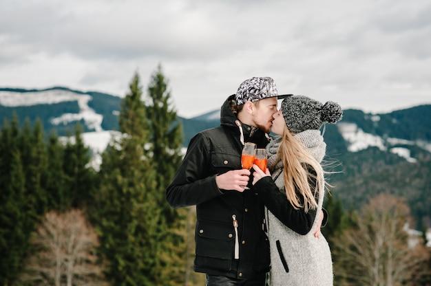 Uomo e donna che tostano con bicchieri di champagne sulla montagna invernale.
