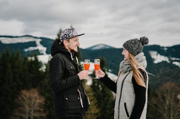 Uomo e donna che tostano con bicchieri di champagne sul picnic di notte invernale sulla montagna. romantica storia d'amore su un tramonto. ragazza e ragazzo. idee per proposte. tempo di festa di natale.
