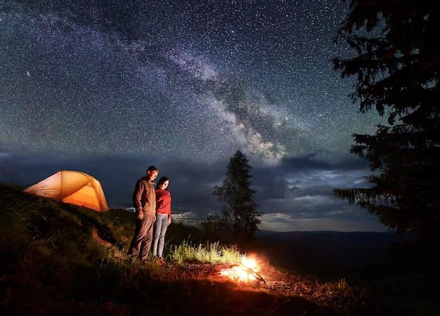 I turisti uomo e donna sono in piedi accanto al campeggio e alla tenda arancione, guardando il falò sotto il bellissimo cielo stellato