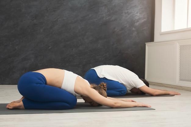 Uomo e donna che allenano lo yoga nella posa del bambino, copia dello spazio. la giovane coppia sportiva fa esercizio di aerobica insieme sul tappetino in palestra