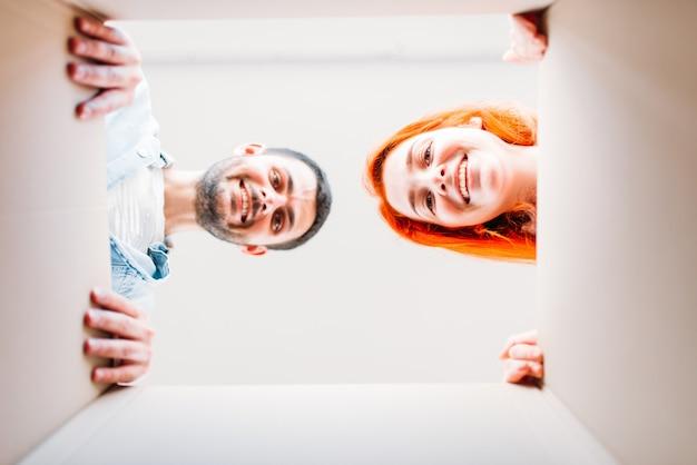 Uomo e donna, vista dall'interno della scatola di cartone