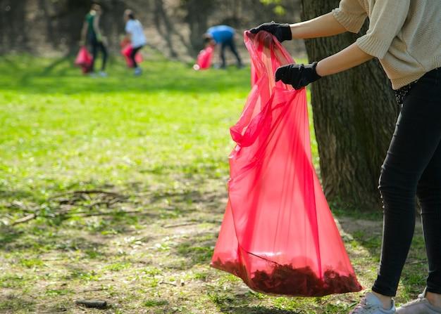 L'uomo e la donna che indossano volontari raccolgono rifiuti e rifiuti di plastica nel parco pubblico. giovani che indossano guanti e mettono i rifiuti in sacchetti di plastica rossi all'aperto