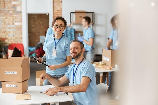 Volontari uomo e donna che sorridono alla telecamera felici di lavorare insieme al progetto di donazione al chiuso