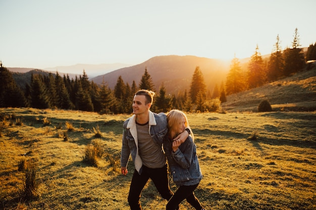 Uomo e donna che camminano sulla montagna al tramonto.