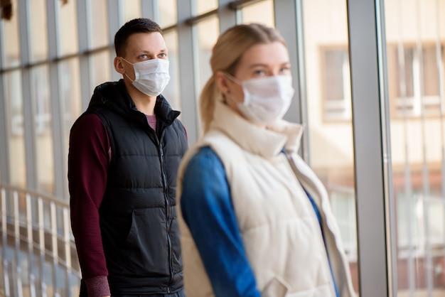 Uomo e donna che indossano una maschera protettiva contro le malattie infettive trasmissibili e come protezione contro l'influenza. nuovo coronavirus 2019-ncov dalla cina