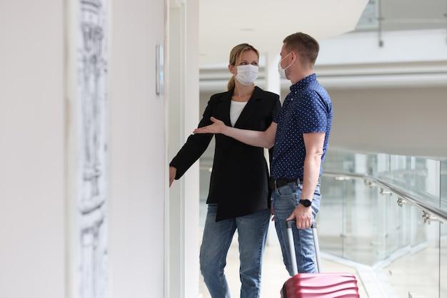 Uomo e donna che indossano maschere mediche protettive che aprono la porta della camera d'albergo