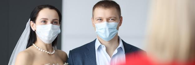 Uomo e donna in abiti da sposa e maschere protettive mediche ai matrimoni cerimoniali nel coronavirus