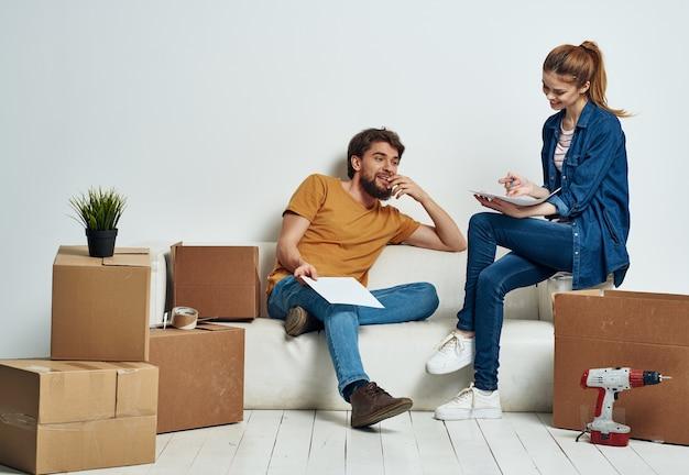 Uomo e donna su scatole di cartone interne divano bianco