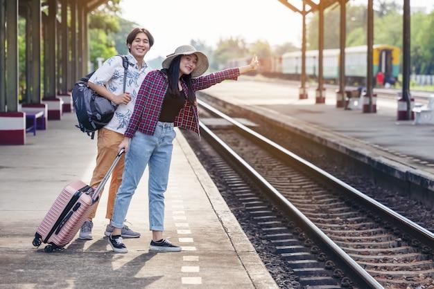 Uomo e donna con zaino in attesa del treno alla stazione ferroviaria. amorevole coppia viaggiatore viaggia insieme in vacanza