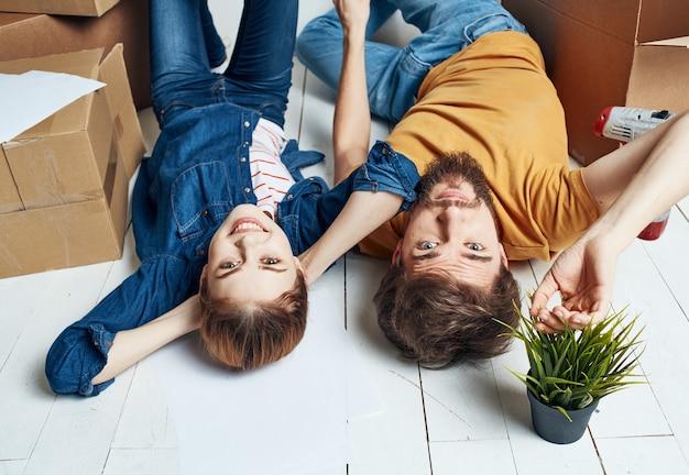 Uomo e donna con scatole sul pavimento un fiore in una pentola in movimento per riparare i lavori.