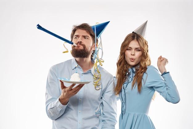 Uomo e donna con berretti in testa vacanza e divertente sorpresa di compleanno