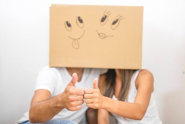 L'uomo e la donna con una scatola di cartone sulla testa pollice in su