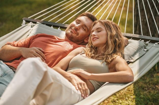 Uomo e donna con gli occhi chiusi sdraiati sull'amaca