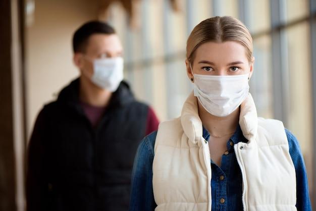 Uomo e donna con maschera facciale medica in aeroporto