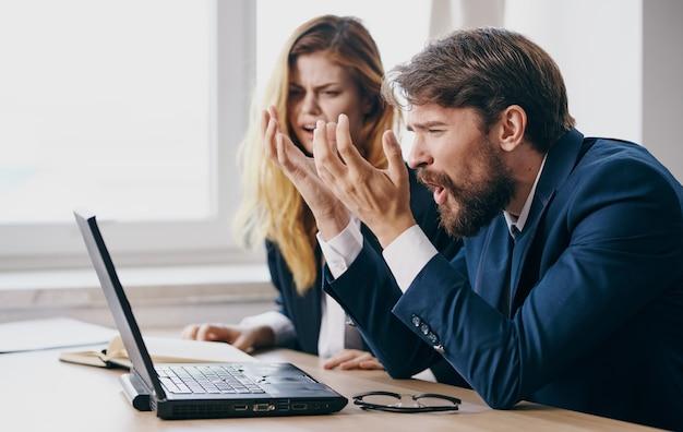 Uomo e donna che lavorano scrivania portatile tecnologia ufficio emozioni comunicazione. foto di alta qualità