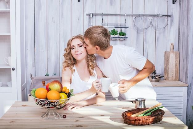 Uomo e donna giovane e bella coppia in cucina cucinare e fare colazione insieme, aiutandosi a vicenda