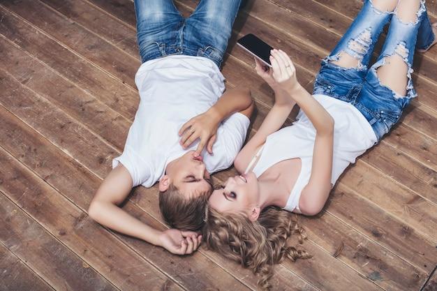 Uomo e donna giovane e bella coppia in camicie bianche che prendono selfie sul pavimento di legno felice