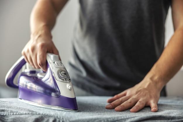 Un uomo al lavoro, che fa i lavori domestici. semplifica l'uso del ferro da stiro premendo leggermente il ferro da stiro sulla camicia sgualcita. il concetto di una moderna vita coniugale di mentalità aperta