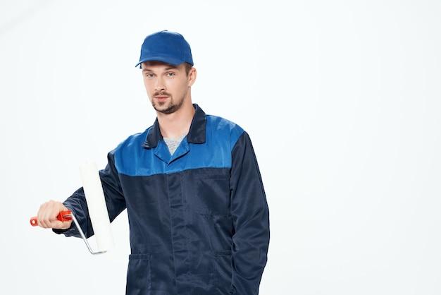 Uomo nel servizio di riparazione della pittura murale dell'uniforme da lavoro