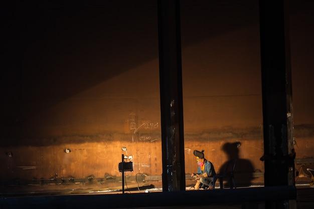 L'uomo lavora la saldatura nel serbatoio dell'industria petrolifera e del gas