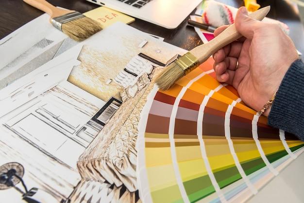 L'uomo lavora con la tavolozza dei colori e lo schizzo dell'appartamento per la casa di design creativo. piano di ristrutturazione dell'architetto