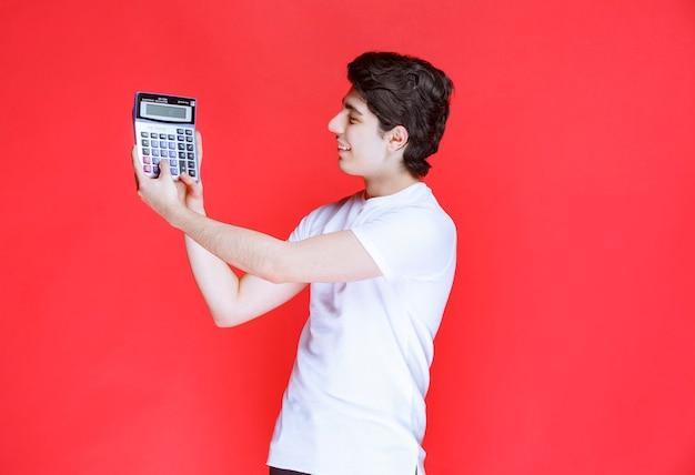 L'uomo ha lavorato alla calcolatrice e sembra soddisfatto del risultato.