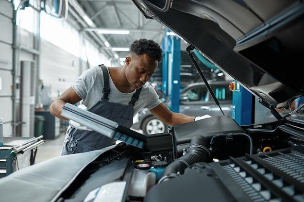Uomo lavoratore cambia olio nel motore in officina meccanica